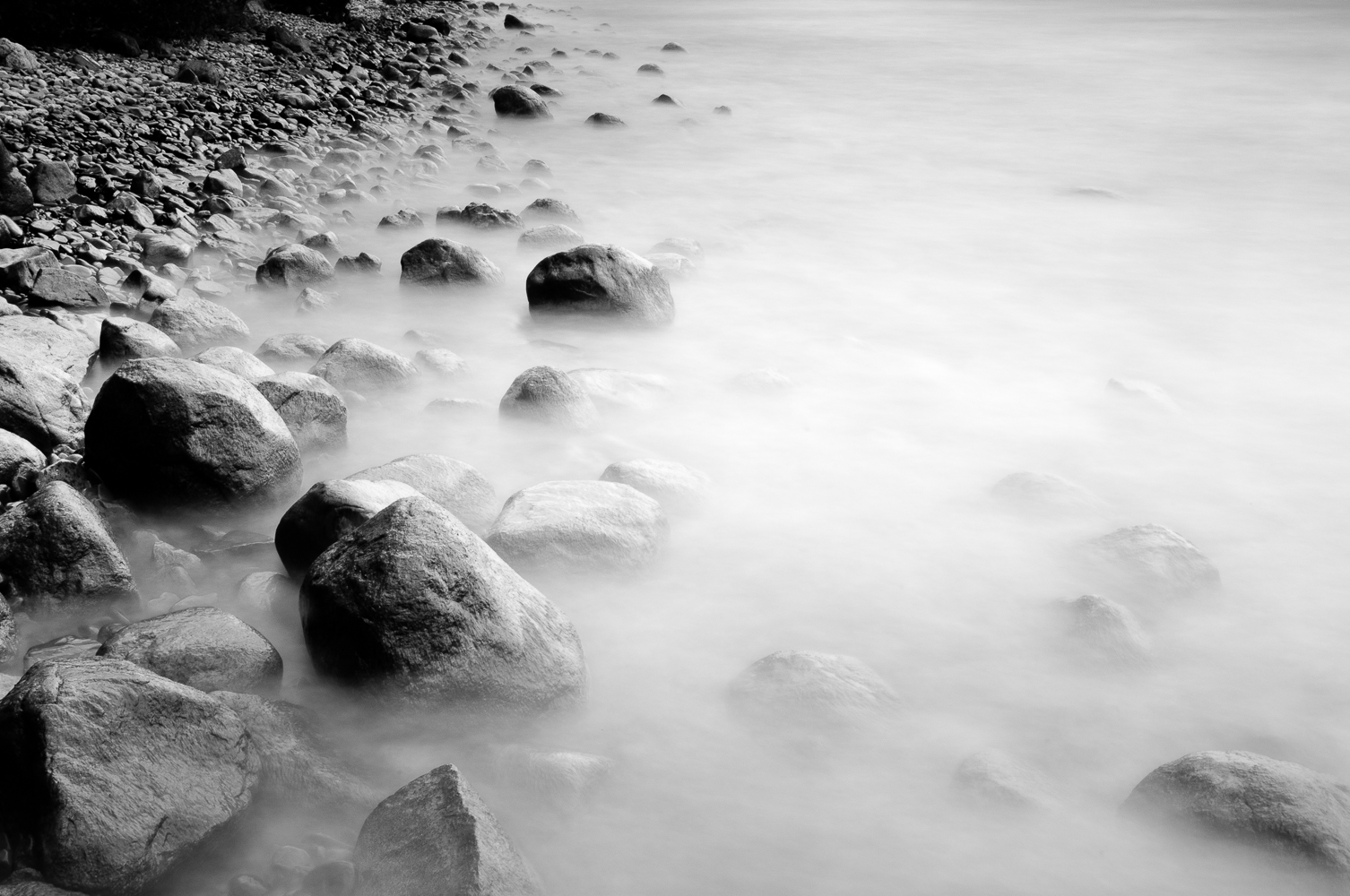 Stones in water by Mark Whitney